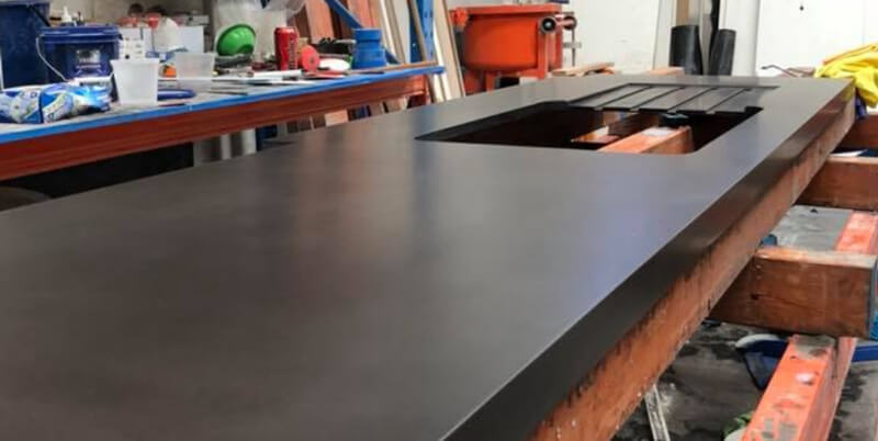 A black concrete kitchen sink being prepared for a Perth home