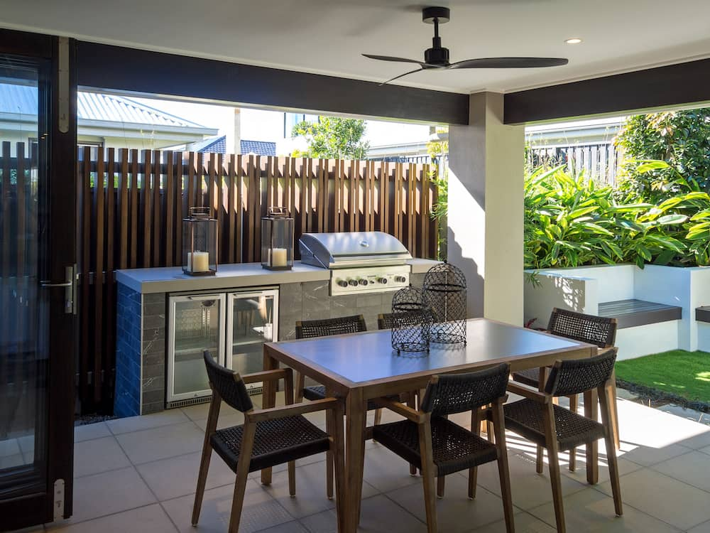 A small outdoor kitchen area with extra concrete bench seating in the background