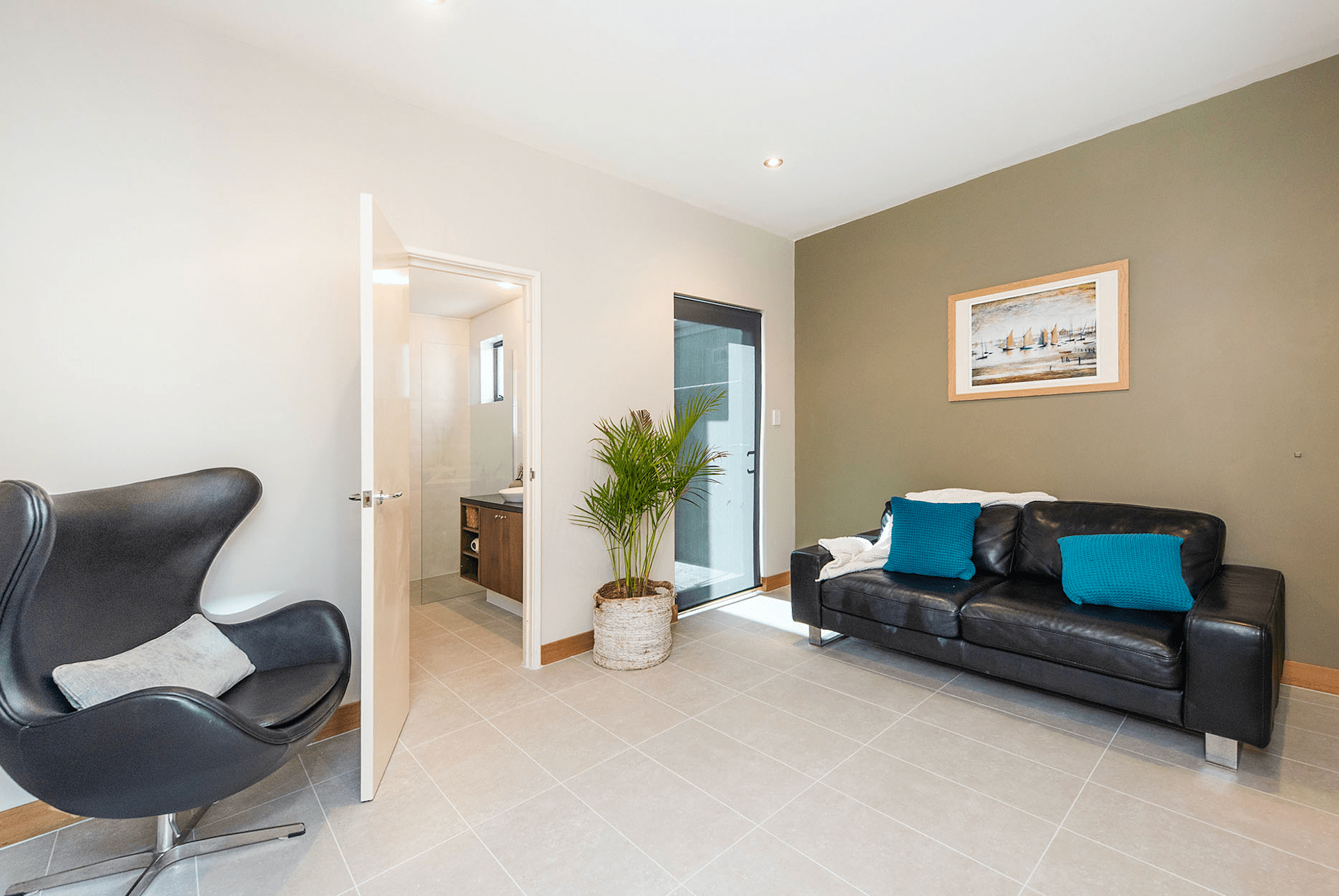 A dashing in-between area of a Cottesloe renovation with dark furniture.