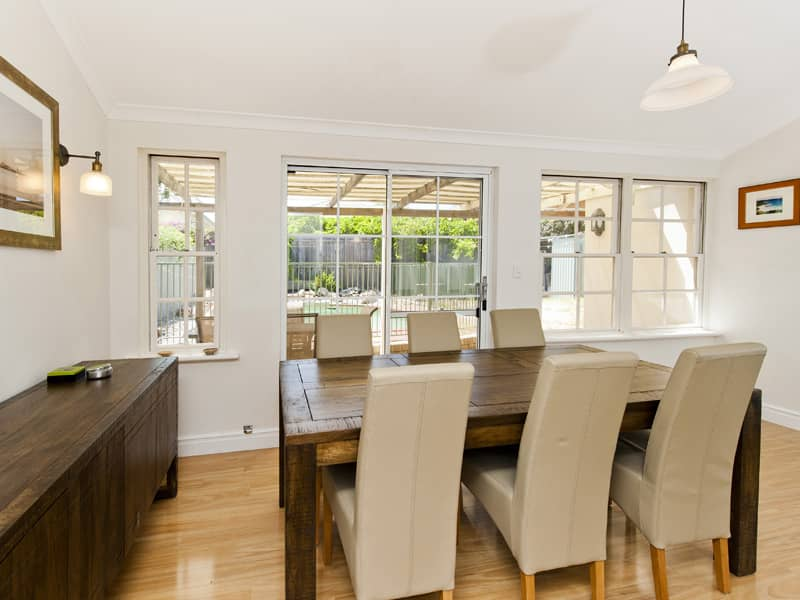 A white dining area finished off with floor boards and cream chairs