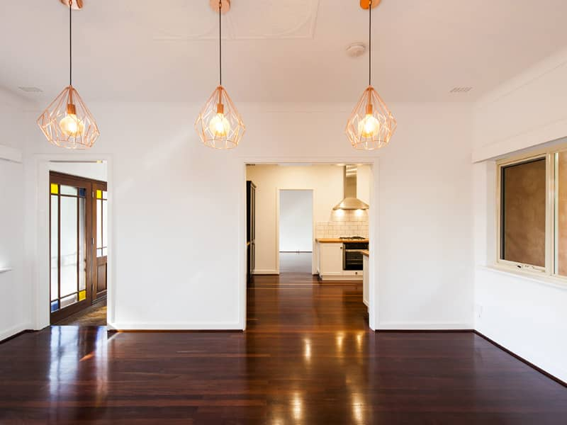 An empty but renovated living area with three new down lights.
