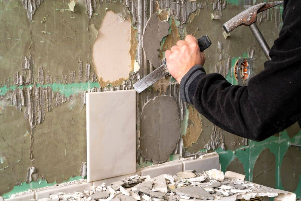 Removing wall tile with chisel and hammer.