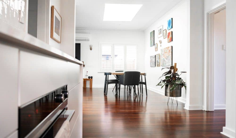 Living room with white walls and wooden flooring.